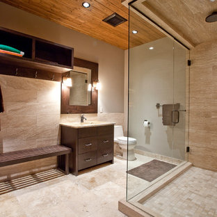 Corner shower - contemporary beige tile and travertine tile corner shower idea in Calgary with flat-panel cabinets and dark wood cabinets