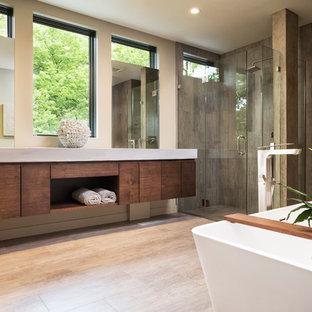 Cette photo montre une petit salle de bain principale moderne avec un placard à porte plane, des portes de placard en bois brun, une baignoire indépendante, une douche à l'italienne, un carrelage beige, un carrelage de pierre, un mur beige, un sol en carrelage de céramique, un lavabo intégré et un plan de toilette en béton.