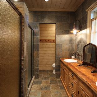 Inspiration for a small rustic master slate tile and brown tile slate floor and brown floor alcove shower remodel in Atlanta with a drop-in sink, recessed-panel cabinets, medium tone wood cabinets, a one-piece toilet, brown walls, wood countertops, a hinged shower door and brown countertops
