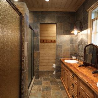 На фото: маленькая главная ванная комната в стиле рустика с накладной раковиной, душем в нише, плиткой из сланца, фасадами с утопленной филенкой, фасадами цвета дерева среднего тона, унитазом-моноблоком, коричневой плиткой, коричневыми стенами, полом из сланца, столешницей из дерева, коричневым полом, душем с распашными дверями и коричневой столешницей с