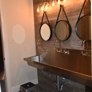 Photo of a large mediterranean family bathroom in Houston with raised-panel cabinets, grey tiles, porcelain tiles, beige walls, porcelain flooring, a trough sink and stainless steel worktops.