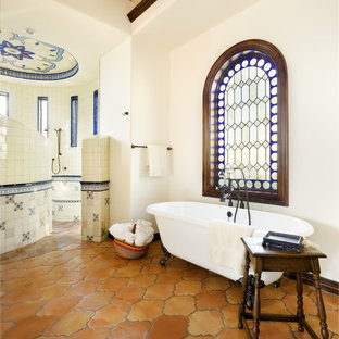 This is an example of a mediterranean bathroom in Austin with a claw-foot tub, terra-cotta tile, terra-cotta floors and a curbless shower.
