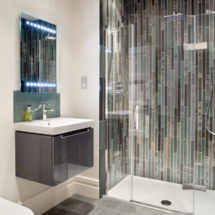 Design ideas for a contemporary shower room bathroom in London with flat-panel cabinets, grey cabinets, an alcove shower, grey tiles, white walls, glass tiles and a wall-mounted sink.