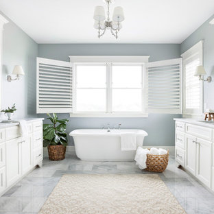 Inspiration for a beach style master marble floor and gray floor freestanding bathtub remodel in Minneapolis with recessed-panel cabinets, white cabinets, gray walls, an undermount sink, gray countertops and marble countertops