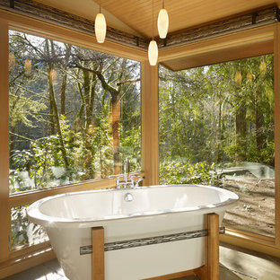 This is an example of a mid-sized midcentury master bathroom in Seattle with a freestanding tub, a curbless shower, stone tile and limestone floors.