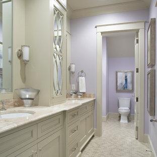Ispirazione per una grande stanza da bagno tradizionale con lavabo sottopiano, ante con riquadro incassato, ante beige, top in pietra calcarea, WC a due pezzi, pareti viola e pavimento in gres porcellanato