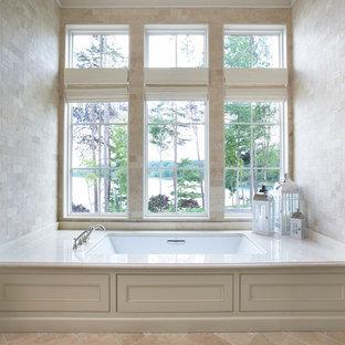 Foto di un'ampia stanza da bagno padronale classica con lavabo sottopiano, ante lisce, ante grigie, top in marmo, vasca sottopiano, piastrelle beige, pareti grigie, pavimento in travertino e piastrelle in travertino