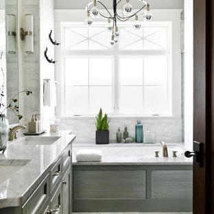 Foto di una stanza da bagno padronale tradizionale con lavabo sottopiano, ante con riquadro incassato, ante grigie, vasca sottopiano, piastrelle bianche e pareti grigie