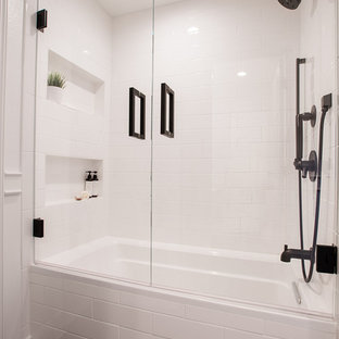 Design ideas for a small transitional 3/4 bathroom in Dallas with white cabinets, a drop-in tub, a shower/bathtub combo, a two-piece toilet, white tile, porcelain tile, white walls, limestone floors, an undermount sink, engineered quartz benchtops, black floor, a hinged shower door and white benchtops.
