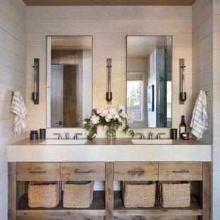 Diseño de cuarto de baño rural con armarios con paneles lisos, puertas de armario de madera oscura, paredes beige, lavabo integrado, suelo gris y encimeras beige