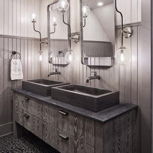 Diseño de cuarto de baño boiserie, rural, boiserie, con armarios con paneles lisos, puertas de armario grises, paredes grises, suelo de baldosas tipo guijarro, lavabo sobreencimera, suelo negro, encimeras grises y boiserie