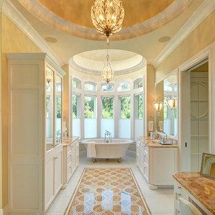 Klassisk inredning av ett mycket stort en-suite badrum, med ett badkar med tassar, en dusch i en alkov, gula väggar, ett undermonterad handfat, luckor med infälld panel, vita skåp och dusch med gångjärnsdörr