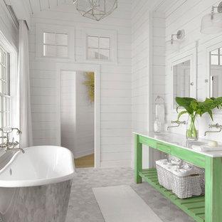 Modelo de cuarto de baño costero con armarios abiertos, puertas de armario verdes, bañera exenta, paredes blancas y lavabo bajoencimera