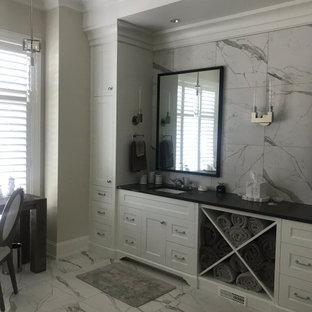 Неиссякаемый источник вдохновения для домашнего уюта: огромная главная ванная комната в стиле современная классика с фасадами в стиле шейкер, белыми фасадами, черно-белой плиткой, мраморной плиткой, бежевыми стенами, мраморным полом, врезной раковиной, столешницей из искусственного кварца, белым полом, черной столешницей, унитазом, тумбой под две раковины и встроенной тумбой