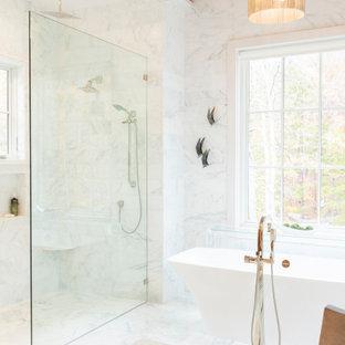 Idéer för att renovera ett stort maritimt vit vitt en-suite badrum, med öppna hyllor, ett fristående badkar, en kantlös dusch, en toalettstol med separat cisternkåpa, vit kakel, porslinskakel, vita väggar, marmorgolv, ett undermonterad handfat, marmorbänkskiva, vitt golv och med dusch som är öppen