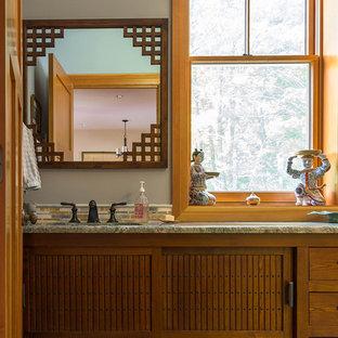 Foto de cuarto de baño principal, de estilo zen, grande, con armarios con paneles lisos, puertas de armario de madera oscura, baldosas y/o azulejos multicolor, azulejos en listel, paredes grises, lavabo bajoencimera y encimera de granito