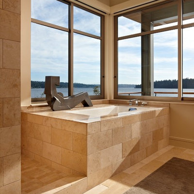 Example of a minimalist limestone tile bathroom design in Seattle with an undermount tub