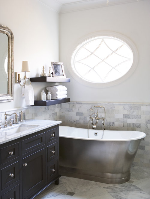 large traditional master bathroom idea in other with a tub subway tile black