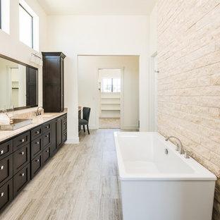 Ejemplo de cuarto de baño principal, clásico renovado, grande, con armarios con paneles lisos, puertas de armario marrones, bañera exenta, encimera de granito, sanitario de dos piezas, paredes blancas, suelo vinílico y lavabo bajoencimera