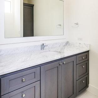 Exemple d'une grande salle de bain principale chic avec un placard à porte plane, des portes de placard marrons, une baignoire indépendante, un plan de toilette en granite, un WC à poser, un mur blanc, un sol en marbre et une vasque.