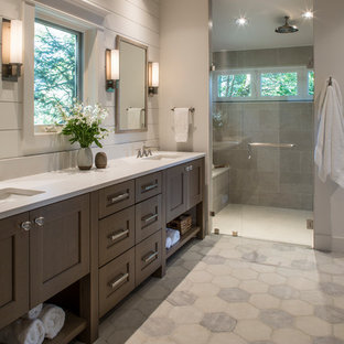 Photo of a mid-sized transitional master bathroom in Other with furniture-like cabinets, medium wood cabinets, a double shower, a two-piece toilet, gray tile, ceramic tile, white walls, ceramic floors, an undermount sink, engineered quartz benchtops, grey floor, a hinged shower door and white benchtops.