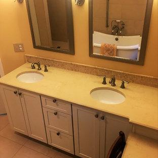 グランドラピッズの中サイズのトラディショナルスタイルのおしゃれなマスターバスルーム (インセット扉のキャビネット、白いキャビネット、置き型浴槽、段差なし、一体型トイレ、ベージュのタイル、磁器タイル、黄色い壁、磁器タイルの床、一体型シンク、珪岩の洗面台) の写真