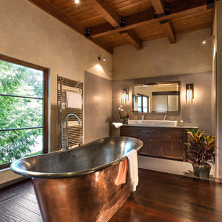Photo of a rustic ensuite bathroom in Milwaukee with recessed-panel cabinets, a freestanding bath, an alcove shower, a one-piece toilet, grey tiles, stone tiles, beige walls, dark hardwood flooring, a trough sink and dark wood cabinets.