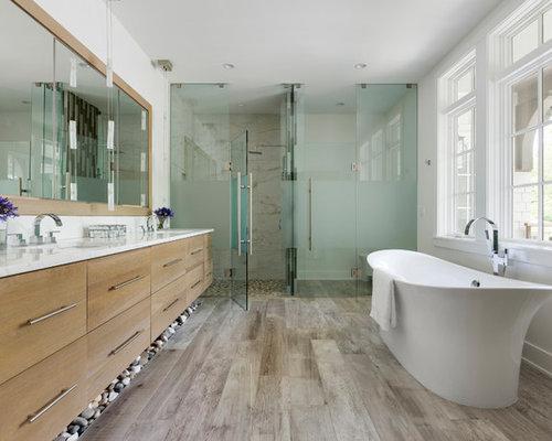 Landhaus Badezimmer Mit Flächenbündigen Schrankfronten, Hellbraunen  Holzschränken, Freistehender Badewanne, Bodengleicher Dusche, Beigefarbenen