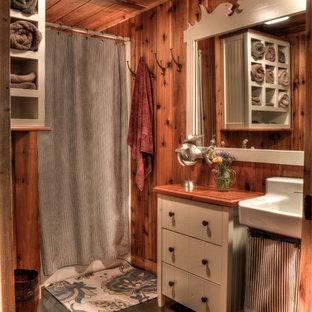 Diseño de cuarto de baño rústico con suelo de madera pintada, lavabo tipo consola, puertas de armario beige, encimera de madera, bañera empotrada y combinación de ducha y bañera