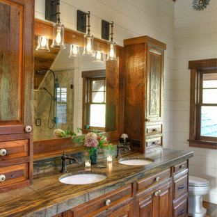Inspiration for a large rustic master dark wood floor and brown floor bathroom remodel in Minneapolis with raised-panel cabinets, dark wood cabinets, white walls, an undermount sink, granite countertops, a hinged shower door and green countertops