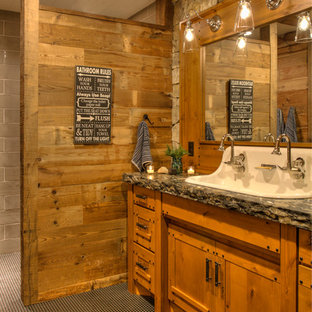 Design ideas for a mid-sized country kids bathroom in Minneapolis with furniture-like cabinets, medium wood cabinets, a trough sink, porcelain floors, granite benchtops, black floor and black benchtops.