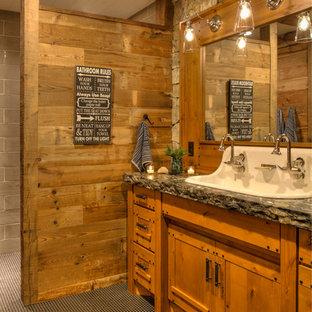 ミネアポリスの中サイズのラスティックスタイルのおしゃれな子供用バスルーム (家具調キャビネット、中間色木目調キャビネット、横長型シンク、磁器タイルの床、御影石の洗面台、黒い床、黒い洗面カウンター) の写真