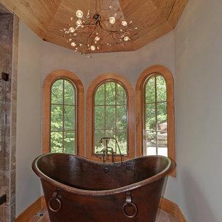 Imagen de cuarto de baño rural con bañera exenta y suelo de baldosas de terracota