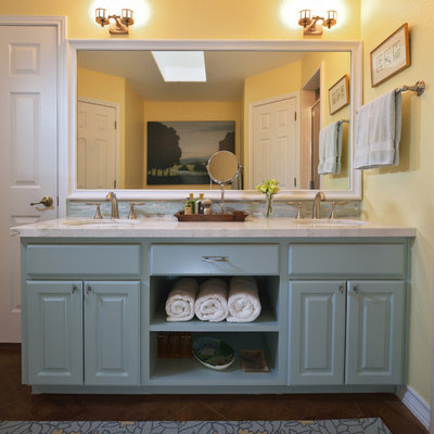 Alcove shower - mid-sized traditional master blue tile concrete floor alcove shower idea in Austin with an undermount sink, raised-panel cabinets, blue cabinets, marble countertops, a two-piece toilet and yellow walls