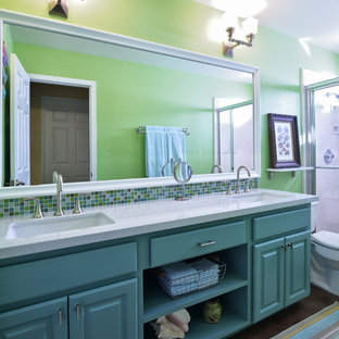 This is an example of a mid-sized traditional 3/4 bathroom in Austin with an undermount sink, raised-panel cabinets, turquoise cabinets, an alcove shower, a two-piece toilet, multi-coloured tile, quartzite benchtops, green walls and concrete floors.