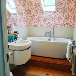 Ispirazione per una piccola stanza da bagno padronale shabby-chic style con ante lisce, ante bianche, vasca freestanding, WC monopezzo, piastrelle blu, piastrelle di vetro, pareti rosa, pavimento in legno massello medio, lavabo integrato, top in superficie solida, pavimento marrone e top bianco