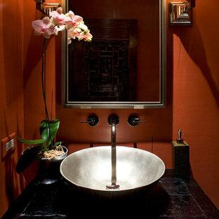 Ispirazione per una piccola stanza da bagno con doccia etnica con lavabo a bacinella, consolle stile comò, ante nere, WC monopezzo, pareti rosse e pavimento in pietra calcarea