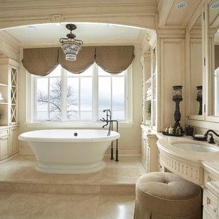 Modelo de cuarto de baño principal, tradicional, grande, con armarios con paneles empotrados, puertas de armario con efecto envejecido, bañera exenta, baldosas y/o azulejos beige y lavabo bajoencimera