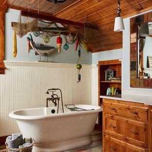 Imagen de cuarto de baño principal, rural, de tamaño medio, con puertas de armario de madera oscura, bañera exenta, paredes azules, encimera de granito, suelo multicolor, armarios tipo mueble, baldosas y/o azulejos azules y suelo de madera pintada