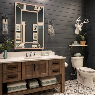 Alcove shower - small beach style 3/4 white tile and cement tile cement tile floor and multicolored floor alcove shower idea with shaker cabinets, medium tone wood cabinets, a two-piece toilet, black walls, an undermount sink, engineered quartz countertops and a hinged shower door