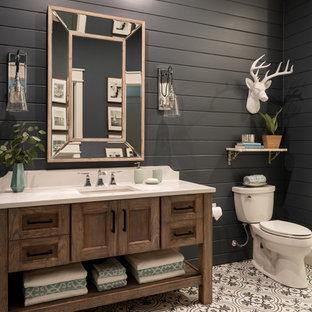 小さいビーチスタイルのおしゃれなバスルーム (浴槽なし) (シェーカースタイル扉のキャビネット、中間色木目調キャビネット、アルコーブ型シャワー、分離型トイレ、白いタイル、黒い壁、セメントタイルの床、アンダーカウンター洗面器、クオーツストーンの洗面台、マルチカラーの床、開き戸のシャワー、セメントタイル) の写真