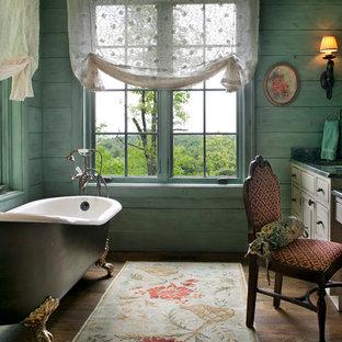 Réalisation d'une salle de bain victorienne avec un placard avec porte à panneau surélevé, une baignoire sur pieds, un mur bleu et un plan de toilette vert.