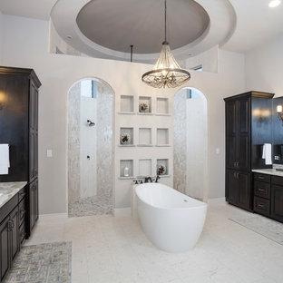 オースティンの大きいトランジショナルスタイルのおしゃれなマスターバスルーム (置き型浴槽、段差なし、分離型トイレ、大理石タイル、ライムストーンの床、アンダーカウンター洗面器、グレーの洗面カウンター、レイズドパネル扉のキャビネット、濃色木目調キャビネット、ベージュのタイル、白い壁、珪岩の洗面台、ベージュの床、オープンシャワー) の写真