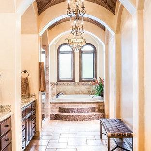 Idées déco pour une salle de bain méditerranéenne avec un placard avec porte à panneau surélevé, des portes de placard en bois sombre, une baignoire posée, un carrelage beige et un mur beige.