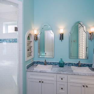 Bild på ett mellanstort amerikanskt badrum för barn, med luckor med infälld panel, vita skåp, en dubbeldusch, flerfärgad kakel, stenkakel, blå väggar, klinkergolv i porslin, ett undermonterad handfat och granitbänkskiva