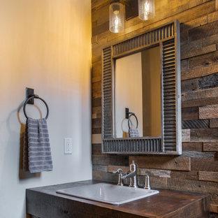 Modelo de cuarto de baño madera, rústico, pequeño, madera, con puertas de armario de madera en tonos medios, paredes beige, lavabo encastrado, encimera de madera y madera