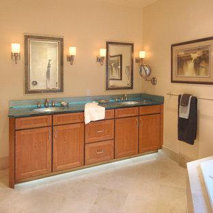 Foto di una grande stanza da bagno padronale classica con ante con riquadro incassato, ante in legno scuro, vasca da incasso, doccia a filo pavimento, pareti beige, pavimento in pietra calcarea, lavabo sottopiano e top in vetro