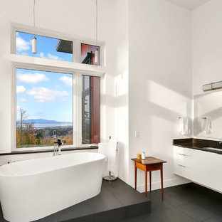Japanese bathtub - contemporary white tile slate floor and black floor japanese bathtub idea in Seattle with flat-panel cabinets, white cabinets, white walls, an undermount sink, granite countertops and black countertops