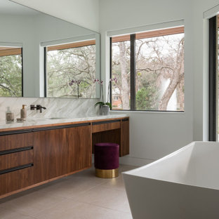 Свежая идея для дизайна: главная ванная комната в современном стиле с плоскими фасадами, темными деревянными фасадами, отдельно стоящей ванной, разноцветной плиткой, плиткой из листового камня, белыми стенами, врезной раковиной, бежевым полом и разноцветной столешницей - отличное фото интерьера