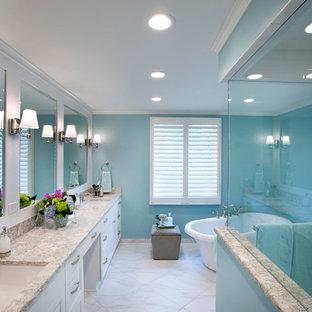 Modelo de cuarto de baño principal, tradicional, grande, con armarios con paneles empotrados, puertas de armario blancas, bañera exenta, baldosas y/o azulejos blancos, baldosas y/o azulejos de piedra, paredes azules, suelo de baldosas de porcelana, lavabo bajoencimera y encimera de cuarzo compacto